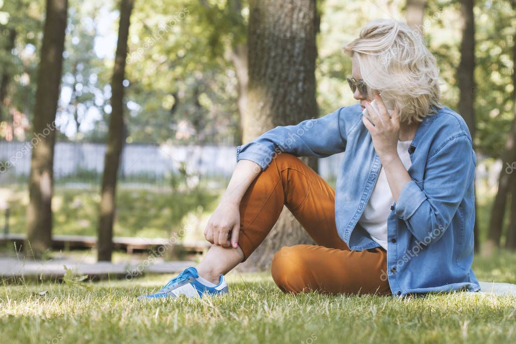 Young woman sitting on green grass in park and talking on mobile phone