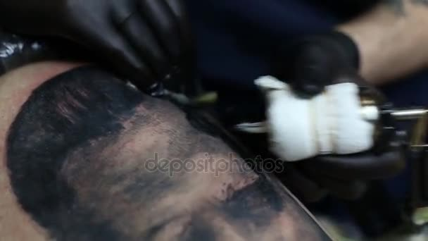 Tattoo master in black gloves, tattooing on the skin