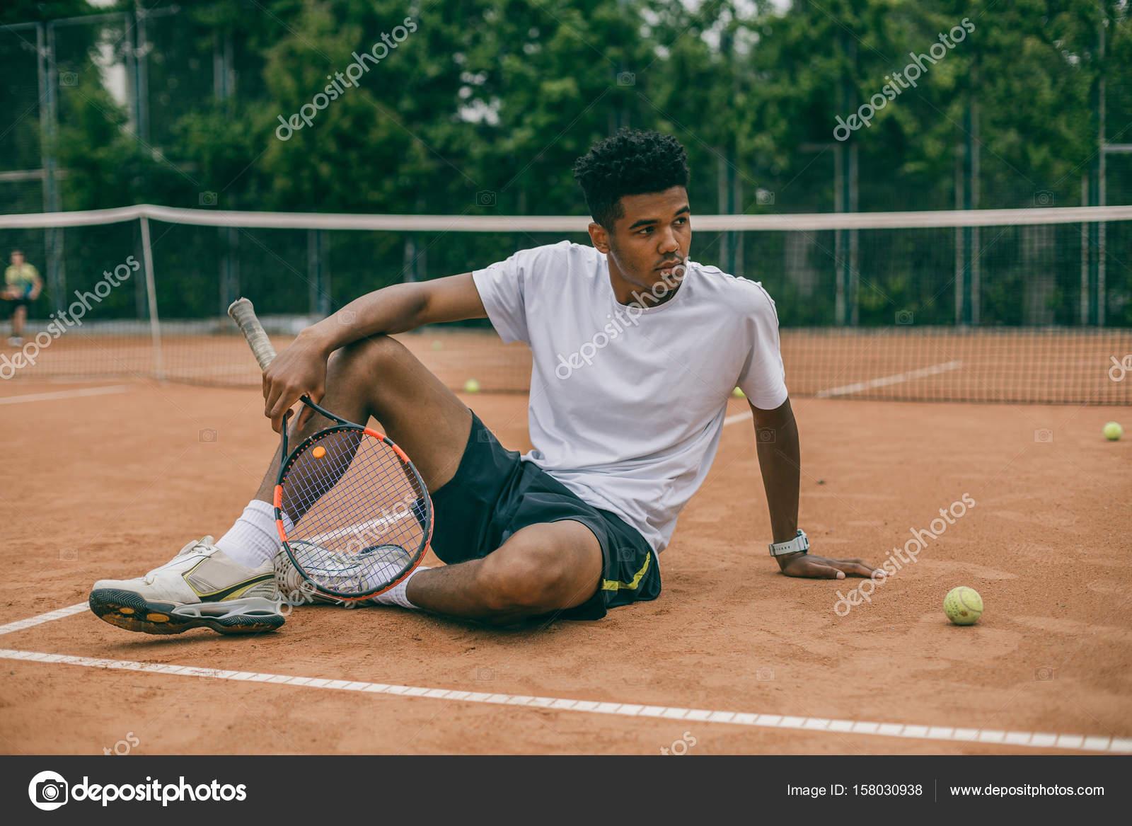 Tennisspieler die nach dem tennisspiel auf boden sa en for 2533 raumgestaltung und entwerfen