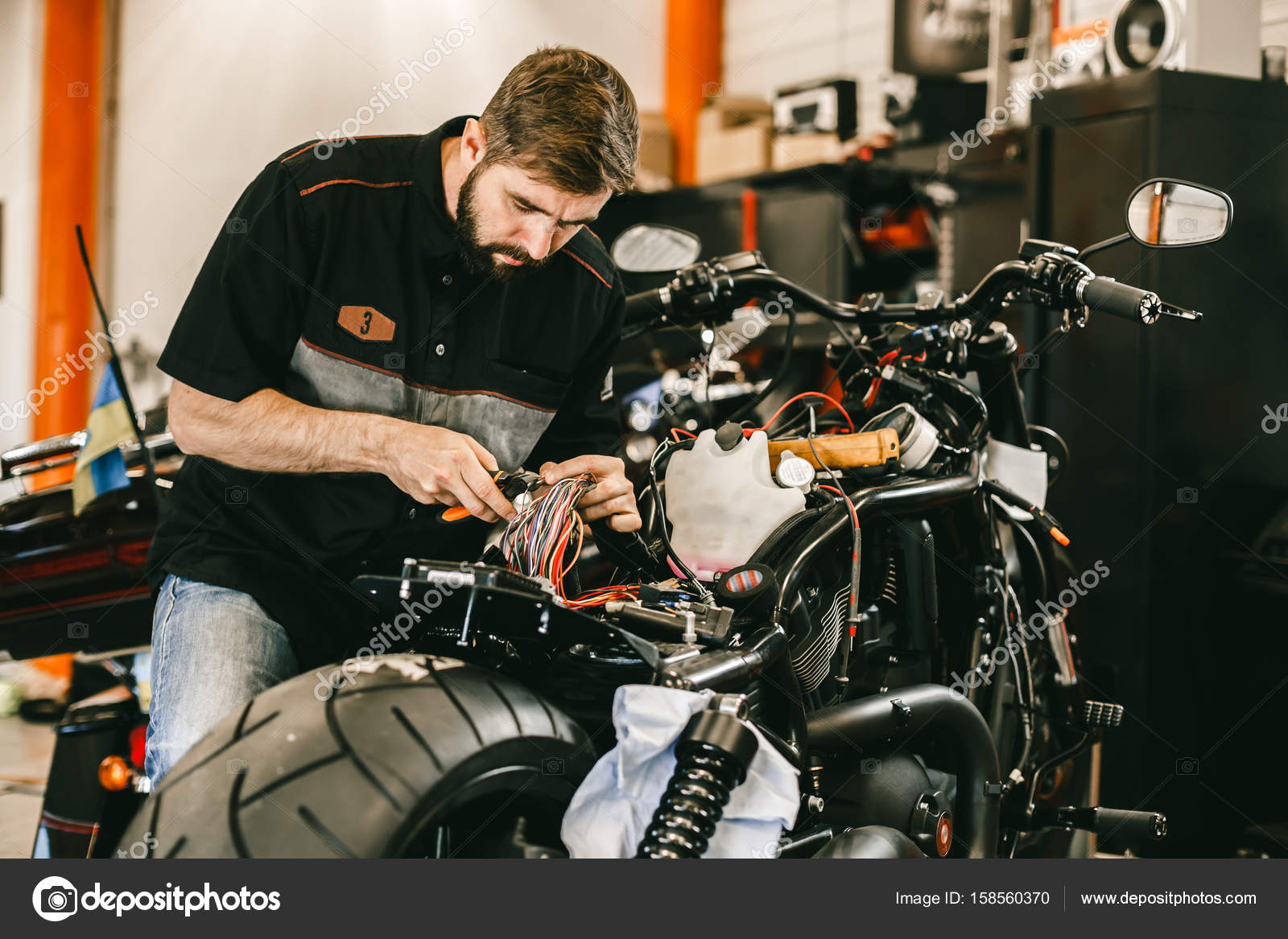 professional motorcycle mechanic works with electronics cuts wires stock photo