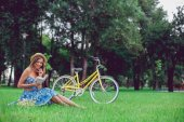 Young female relaxing on a green grass with bicycle in a park on a sunny day.