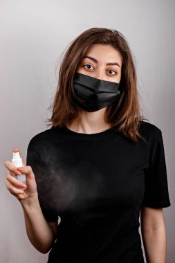 Studio portrait of young woman wearing a face mask, looking at camera, close up, isolated on white background. Flu epidemic, dust allergy, protection against virus. City air pollution concept