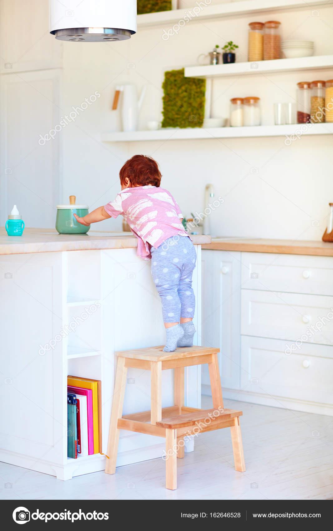 niedlichen Kleinkind Baby klettert auf Tritthocker, versuchen, Dinge ...