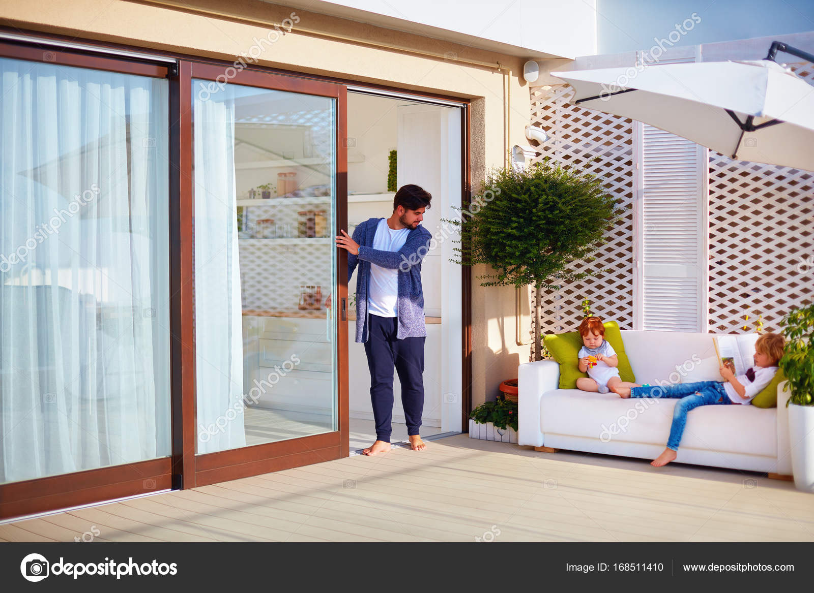 Family relaxing outdoor on rooftop patio with open space kitchen and sliding doors \u2014 Stock Photo & family relaxing outdoor on rooftop patio with open space kitchen and ...