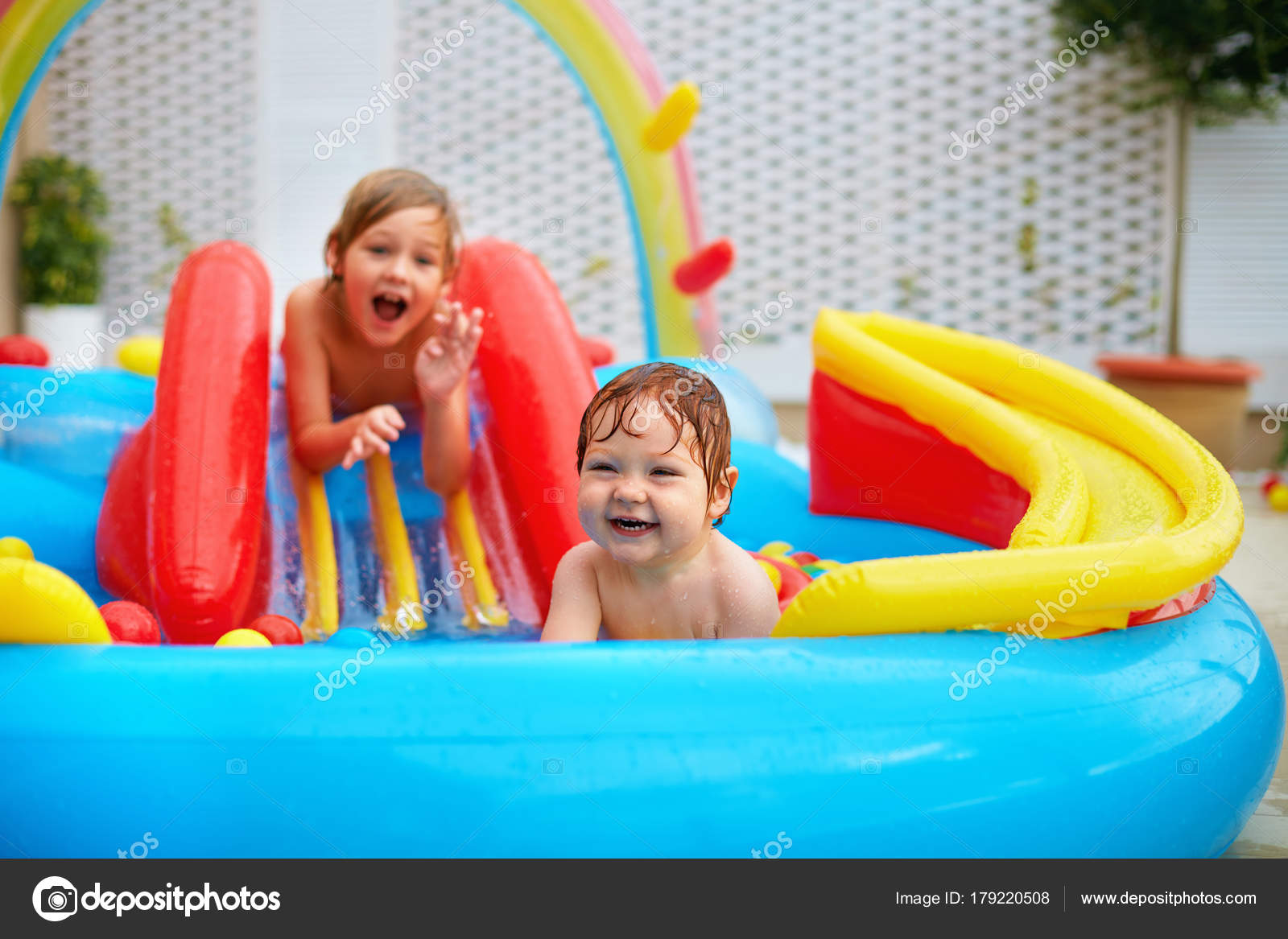 excited kids, family having fun in colorful inflatable pool on patio ...