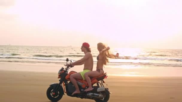 Dva na koni motocyklu na pláži nedaleko vody při západu slunce