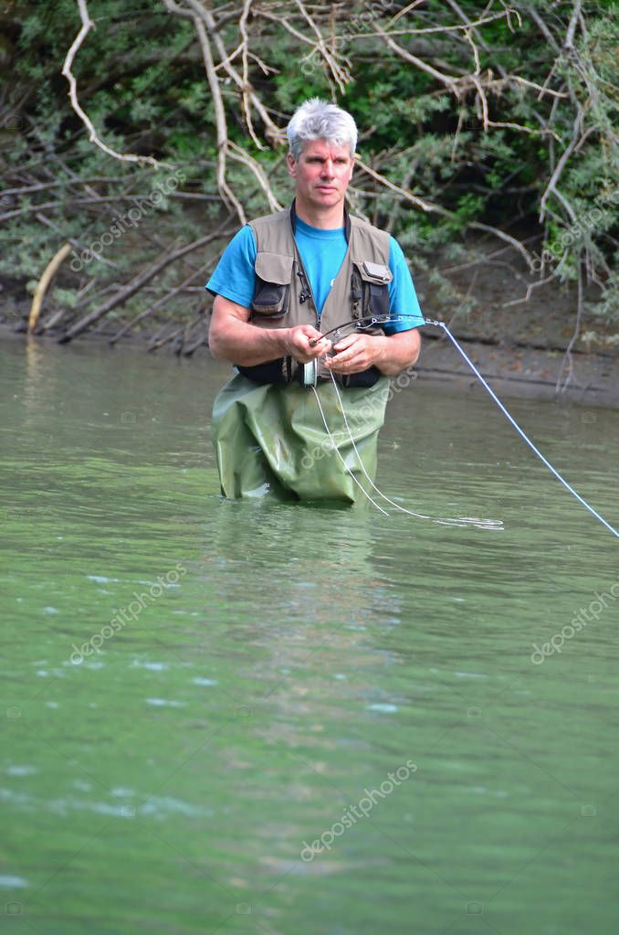 man fly fishing in river thigh deep in water