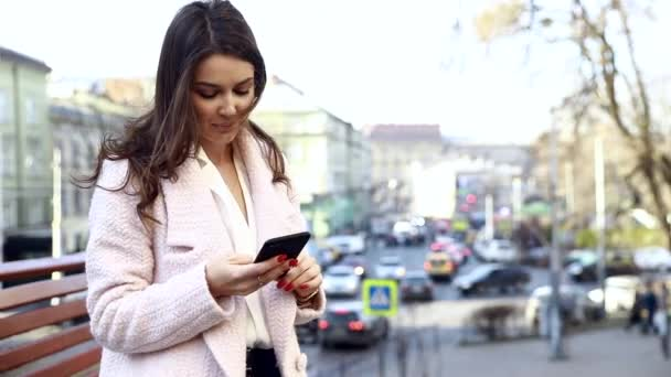 hübsches europäisches Mädchen, das auf einer Bank sitzt und ihr Handy mit Kaffee in der Hand benutzt. Porträt einer Dame mit dunklem lockigem Haar in rosa Mantel, die am Tisch auf der Straße sitzt.