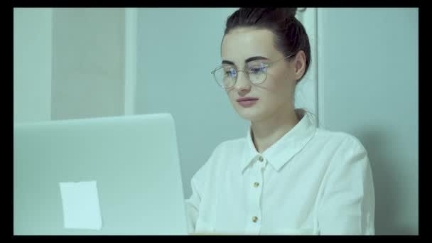 Krásná a kreativní mladá žena sedí u svého stolu pomocí přenosného počítače. Na pozadí světlý úřad, kde pracuje rozmanitý tým mladých profesionálů