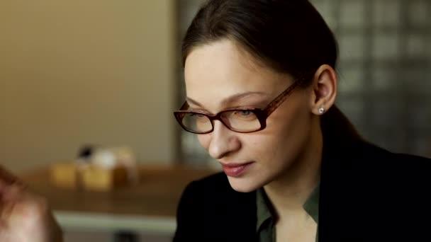 Szép mosolygós üzletasszony stílusos szemüvegben ül a kávézóasztalnál, laptopon dolgozik, kamerába néz