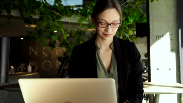 gyönyörű nő elegáns szemüvegben, kezében kávépapír pohár, és nézi okostelefon, miközben ül a kávézóban. Boldog nő használja a mobilját. Üzletasszony kávét iszik és mosolyog.