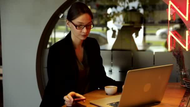 Koncentrált üzletasszony elegáns szemüvegben ülni kávézó dolgozik laptop, koncentrált komoly nő dolgozik a számítógép és a cappuccino a kávézóban, szabadúszó, online tanul, böngészni az interneten, ellenőrzi számlák