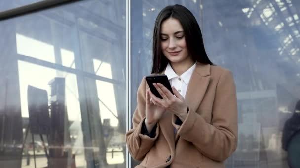 gyönyörű üzletasszony használ okostelefon sms séta vállalati iroda gépelés szöveges üzenetek mobiltelefon ellenőrzése e-mailek sikeres női ügyvezető munkahelyi 4k felvételek