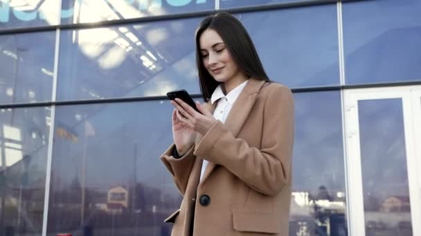 Felnőtt kaukázusi magabiztos fiatal üzletasszony használja Smartphone App kívül közel modern irodaház. Közepes alacsony szögű 4K Lassú mozgás Vállalati felvétel mozgó kamerával