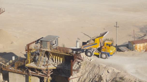 Large dump truck unloads the raw crushed stone crusher.
