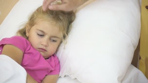 krankes kleines Mädchen, das seine Temperatur hat. Kind mit Fieber: Frau streicht dem Kind über den Kopf. Nahaufnahme.