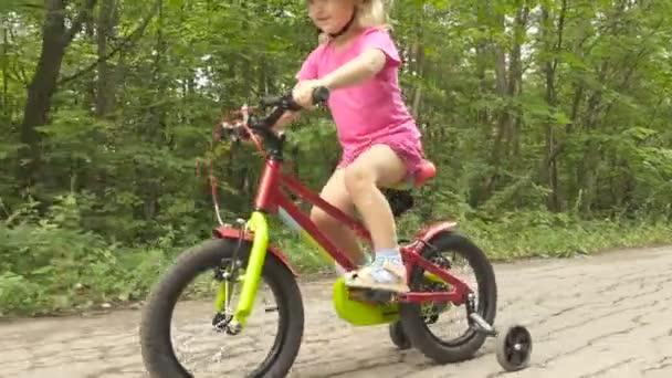 Šťastné dítě jízdě na kole v přírodě. Roztomilé dítě v bezpečnostní přilbu na kole venku. Malá holčička na červené kolo zdravé předškolní děti letní aktivity.