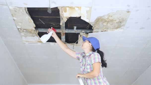 Jonge vrouw schoonmaak schimmel op het plafond. Plafondpanelen ...