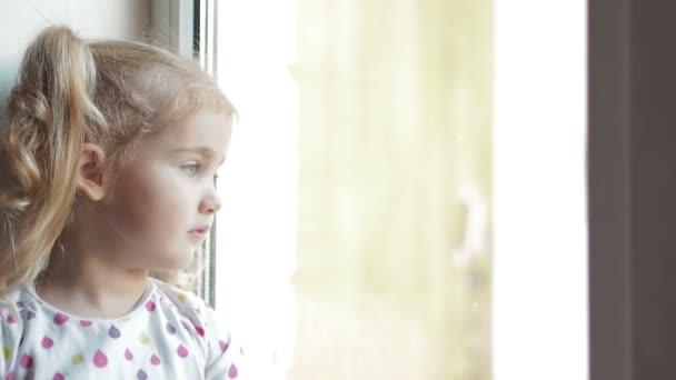 Malá holčička bohužel zírá z okna. Sedí na okenním parapetu. Dítě vypadá z okna.