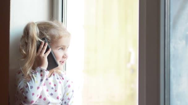 Blond holčička mluví po telefonu. Sedí na okenním parapetu. Dítě vypadá z okna.