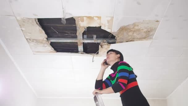 Mladá žena hovor na telefonu v služeb a veřejných služeb. Stropní panely poškozené obrovský otvor ve střeše pronikání dešťové vody. Promočených stropě, pojištění případ