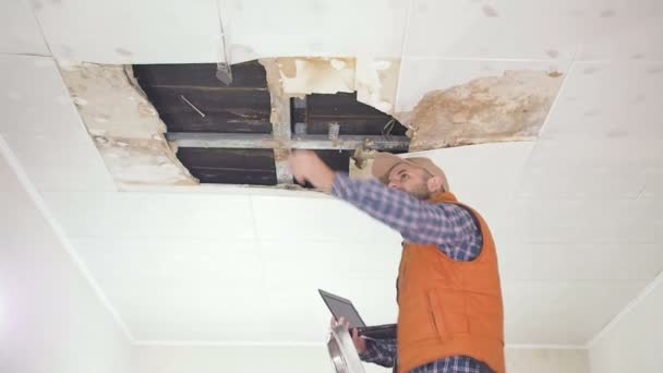 mladý muž dělá inspekci nouzové strop a používání přenosného Pc. veřejné služby. Stropní panely poškozené obrovský otvor ve střeše pronikání dešťové vody. Promočených stropě, pojišťovací agent