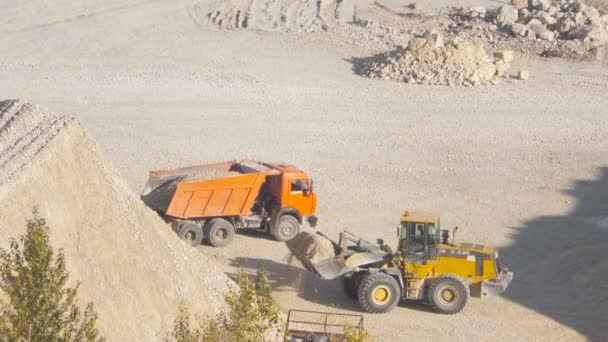 excavator loads a truck rock in the quarry