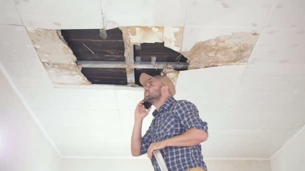 Mladý muž volání na telefonní službě a veřejných služeb. Stropní panely poškozené obrovský otvor ve střeše pronikání dešťové vody. Promočených stropě, pojištění případ