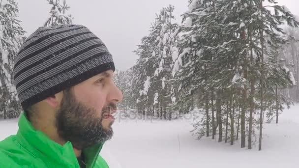 Egy szakállas férfi képmása közelről. Hóesés a parkerdőben. Téli táj havas erdőben. Erős havazás. Hóvihar és a havas út közben egy hideg téli napon
