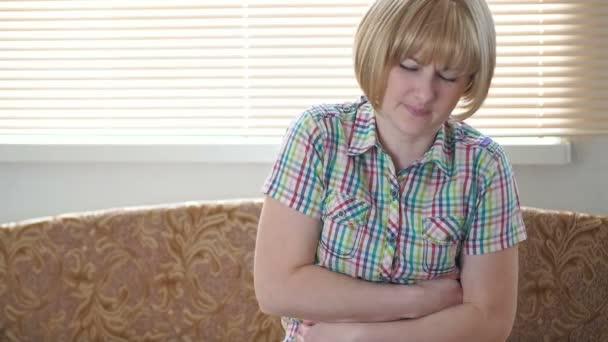 Žena trpící bolesti břicha. Blond dívka trpí sedící u okna