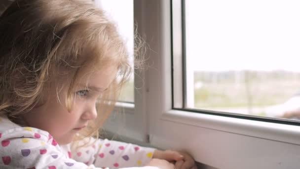 Dítě z okna. Malá holčička vypadá smutně z okna.