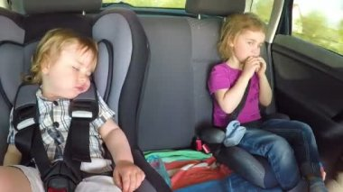 Little children, brother and sister travel in the car on the children's car seats. Time lapse.