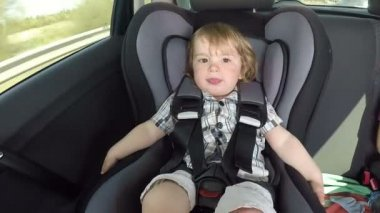 Boy baby kid in a plaid shirt in the children's car seat in the car rides. Little baby child infant an automobile armchair. Time lapse