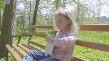 Cute Little girl  writing to notepad, Sitting in the park on the bench.