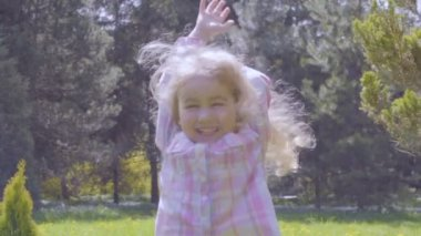 Cute little blonde girl jumping for joy in summer day in park. Slow Motion.