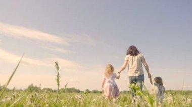 Family mother with her son and daughter are walking around the field. Walk in the fresh air. Summer sunny day. Slow Motion.