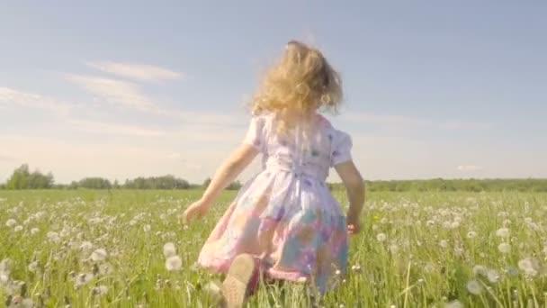 Roztomilá holčička v louce v barvách pampeliška. Radostné veselé dítě směje venku. Letní slunečný den. Zpomalený pohyb.