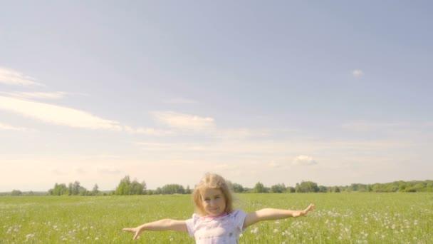 Roztomilá holčička s otevřenou náručí si slunce v oboru. Radostné veselé dítě směje venku. Letní slunečný den. Zpomalený pohyb.
