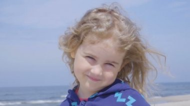 Close up Face Little Girl and Sea. Portrait cute Girl 4 years old standing on the shore.Slow Motion.