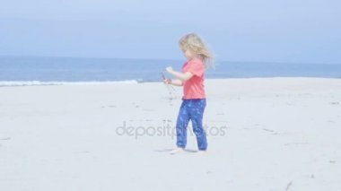 Little girl is cleaning stones, sticks and garbage on the beach.