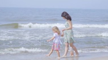 Happy family on the beach. Mother holds the arms of her son and daughter walking along the seashore. Slow motion.