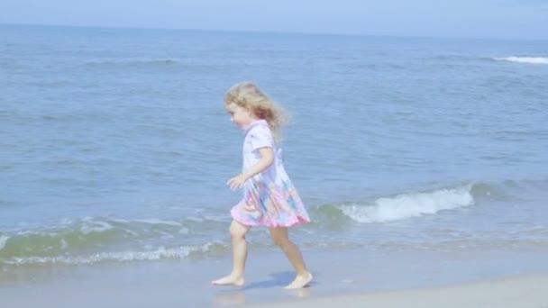 Rozkošná holčička v šatech běží, skákání na pláži. Dítě se těší hrát na pobřeží běží na vodě s radostí. šplouchání v mořských vln. Zpomalený pohyb