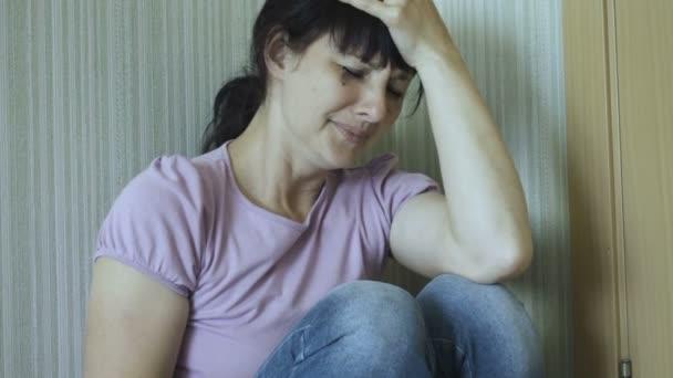 Násilí v rodině. Mladá znásilněné žena pláče zatímco sedí na podlaze v rohu místnosti. Zblízka se bojí a plačící ženy s rozmazaný Make Up. Dívka pláče v rohu a pocit osamění