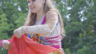 Street artists. A gypsy woman dances in a colorful dress on the city street. Magic dance. Young Witch. Slow motion. Kaliningrad - July 2017 Russian.