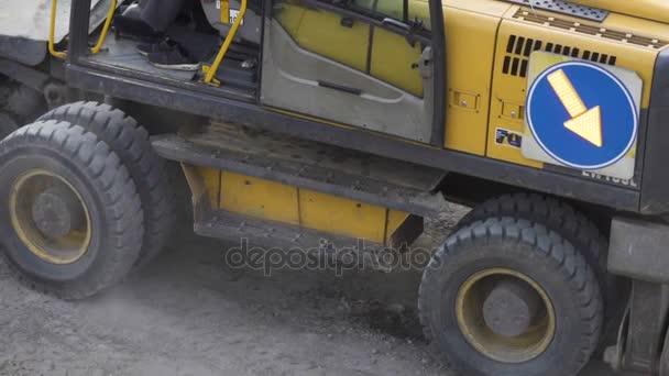 Bagr na kolech se pomalu pohybuje kolem lomu. Detail, Rypadlo nakladač na silniční stavební práce. Bagr traktor funguje na staveništi.