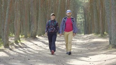 Sports family travels through  forest. A young couple of  tourist with a backpack walk through a forest road. Family travel together, hiking outdoors on nature. Enjoying Nature at Camping.