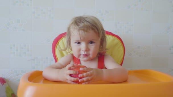 Usmívající se dítě jablko v židlička. Dítě jíst zdravé potraviny. Malý chlapec jíst ovoce. Malý chlapec kousání jablko bílé vysoké židli. Zdravá výživa pro děti