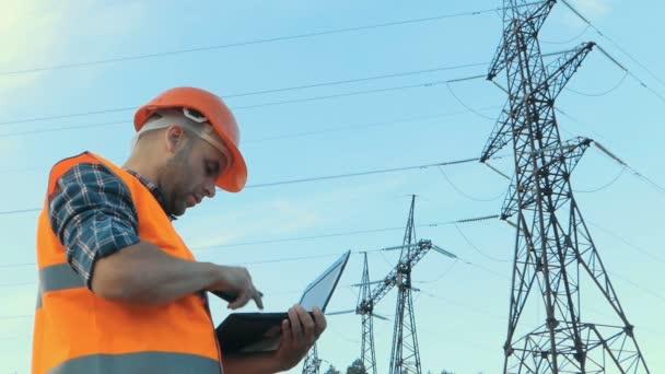 Inženýr pracující. Telefonovat a práci pracovat na notebooku. Kontrola energetických sítí.