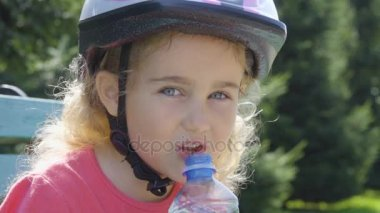 Little girl in protection and helmet drinking water from the plastic bottle, sitting in the park on a green bench. Slow Motion.