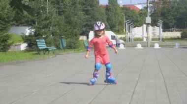 A little girl in a helmet and defense skates on roller skates. The child rolls on the rollers in the park.  Rollerblading In The Park.  Girl learns to ride a roller skate.